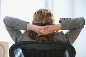 Picture of a businesswoman seated in an office chair with her hands behind he head.