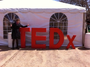 Karen posing by a TEDx sign